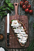 An open-face chicken caprese sandwich covered with melted mozzarella cheese