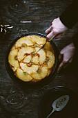 Frau schneidet Upside Down Cake mit Ananas (Aufsicht)