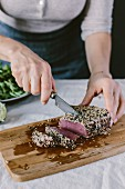 A woman is slicing a sesame crusted and seared yellow fin tuna