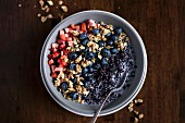 Müslischüssel mit schwarzem Reis, Beeren und Granola (Aufsicht)