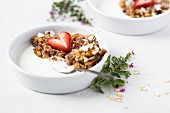 A bowl of Strawberry and Rhubarb Breakfast Oat Crisp is served over yogurt and topped off with a sliced strawberry