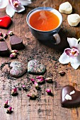 Chocolate candies heart shaped with dry tea roses and tea cup for Valentine s Day