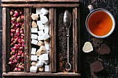 Set of dry black tea, tea roses and sugar cubes in wooden box with vintage tea strainer and cup of tea