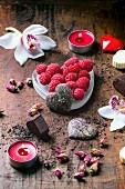 Valentinstag: Pralinen in Herzform zwischen getrockneten Teerosen, Himbeeren und Orchideen