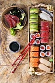 Sushi set nigiri, sashimi and rolls on clay plate served with chopsticks and soy sauce on stone surface