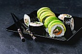 Sushi set with avocado rolls served with chopsticks on square plate over black stone slate