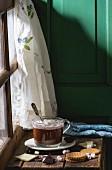 Heiße Schokolade mit Marshmallows in Glastasse auf Fensterbank, daneben Cookies und Fäustlinge