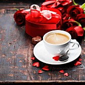 Valentine composition with coffee, roses and gift box on wooden background