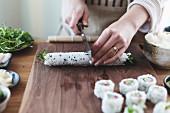 Suhsi zubereiten: Sushirolle in Stücke schneiden