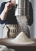 Frau siebt Mehl fürs Backen mit Mehlsieb auf Arbeitsplatte
