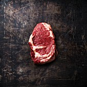 Raw fresh meat Ribeye Steak on dark metal background