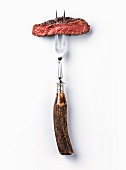 Sliced beef steak ribeye on meat fork on white background