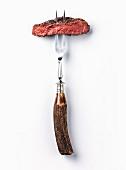 Scheibe vom Ribeye-Steak auf Fleischgabel vor weißem Hintergrund
