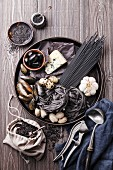 Black raw food ingredients - Pasta, olives, clams on wooden background