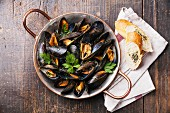 Mussels in copper cooking dish and French Baguette with herbs on wooden background