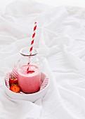 Erdbeersmoothie in einer Glasflasche mit Strohhalm