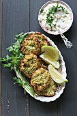 Zucchini fritters on a plate with salsa yogurt dressing