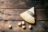 Big piece and little cubes of Belgian cheese with vintage fork over wooden background