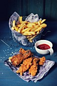 Chicken fries strips and legs on paper with basket of French fries and bowl of ketchup sauce over blue wooden table