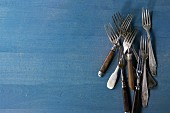 Set of vintage forks over blue wooden surface