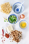 Ingredients for asian ramen soup. Noodles, spring onion, feta cheese, mushrooms, egg and chili pepper