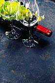 Rotweingläser, Rotweinflasche und Weinblätter auf schwarzem Untergrund