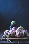 Verschiedene Auberginen auf einem Schneidebrett, ganz und in Scheiben