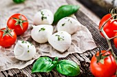 Cherry tomatoes, basil leaves, mozzarella cheese on a wooden background