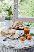 Cheese platter, rustic bread and chutney on white wooden table with flower bouquet and wooden boards