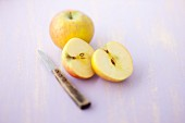 Boskop apples, whole and halved, with a knife