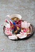 Rose blossom tea and rose petals on a silver plate