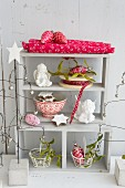 Shelves festively decorated with angels. biscuits, glass ornaments and mistletoe