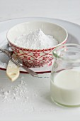 A bowl of icing sugar and a glass of milk for making icing