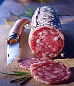 A sliced French salami and an Opinel knife on a wooden board