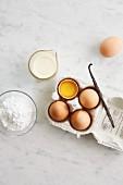 Zutaten für Eiscreme - Sahne, Eigelb, Puderzucker und Vanilleschote