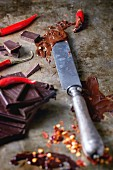 Chopping and melting dark chocolate with fresh and dry red hot chili peppers and vintage knife