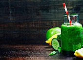 Fresh organic green smoothie with spinach, cucumber, parsley, celery and lemon on wooden background
