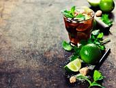 Zutaten für Mojito: Eiswürfel, Minze, Zucker und Limetten vor rustikalen Hintergrund