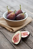 Figs in a bowl on a wooden background