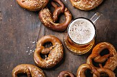 Glass of lager beer with traditional salted pretzels over old dark wooden background