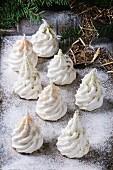 weiße Baiser-Tannenbäumchen mit farbigem Zucker und Matcha-Tee verziert