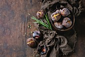 Roasted chestnuts in the ashes with rosemary in tin can on sackcloth over old dark wooden background