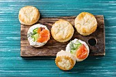 Sliced traditional english cheese scones with smoked salmon, creme cheese and fresh cucumber served with whole scones