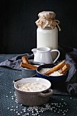 Ingredients for making rice pudding: white uncooked rice, sugar, cinnamon sticks, milk, cream and pot of cooking pudding
