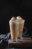 Pumpkin spicy latte with whipped cream and cinnamon in two glasses standing on clay board