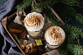 Pumpkin spicy latte with whipped cream and cinnamon in two glasses standing in wooden board with Christmas decoration
