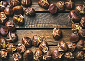 Roasted chestnuts over rustic wooden table background