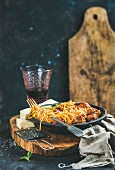 Spaghetti with meatballas, basil and parmesan cheese in black plate and red wine in glass over rustic wooden board