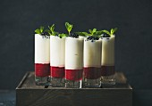 Dessert in glass with blackberries and mint leaves over dark background