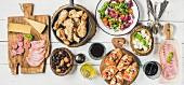 Vorspeisenbuffet mit Hähnchenbeinen, Salat, Oliven, Wurst, Bruschetta und Wein